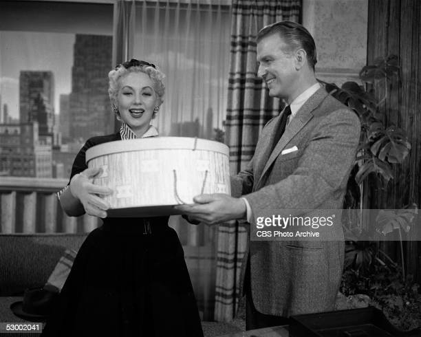 American actress Ann Sothern smiles as she recieves a large hat box from actor Don Porter in a scene from the television series 'Private Secretary'...