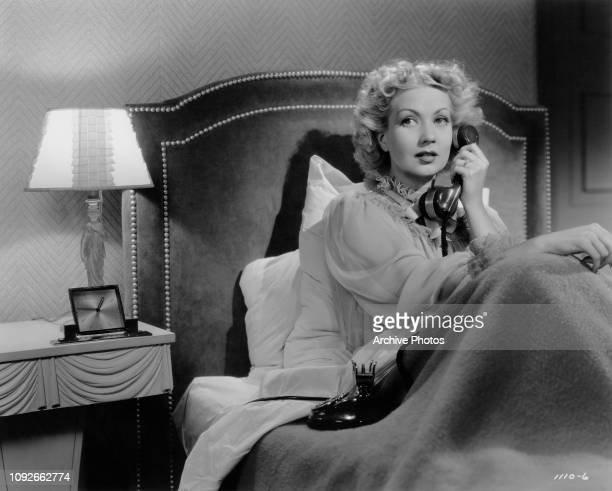 American actress Ann Sothern takes a phone call in bed in a scene from the MGM film 'Fast and Furious' 1939