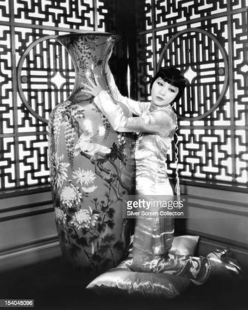 American actress Anna May Wong kneeling by a large oriental vase circa 1930