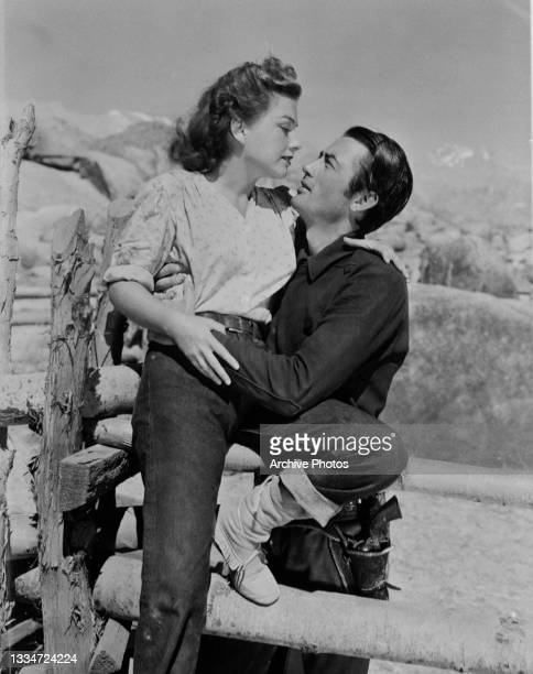 American actress Anne Baxter is held by American actor Gregory Peck sewing in a scene from 'Yellow Sky,' in which Baxter plays Mike and Peck is James...