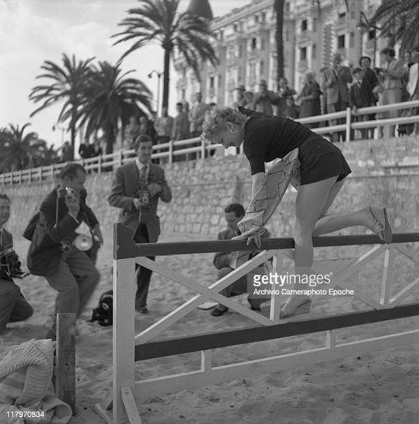 American actress Anne Baxter pictured while stepping a fence on the beach surrounded by photographers with Rolleiflex cameras several fans behind the...