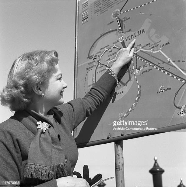 American actress Anne Baxter wearing a coat a scarf and a grapevine leaf brooch pointing a Venice map on a sign Venice 1953