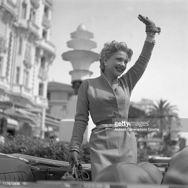 American actress Anne Baxter wearing a tailleur a belt and gloves holding a handbag and sunglasses greeting from a car Cannes 1953
