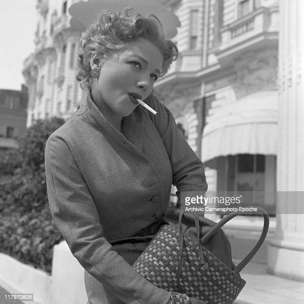 American actress Anne Baxter wearing a tailleur ang gloves a cigarette in her mouth looking for something in her handbag Cannes 1953