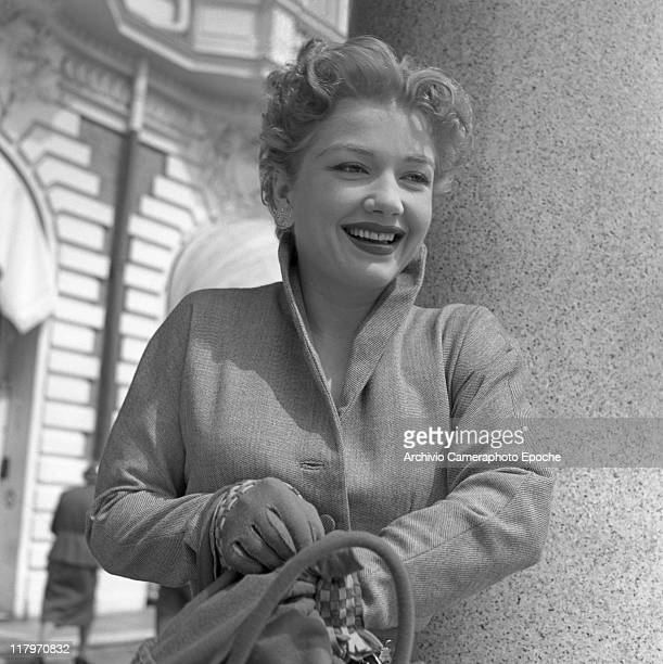 American actress Anne Baxter wearing a tailleur ang gloves looking for something in her handbag Cannes 1953