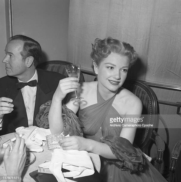 American actress Anne Baxter wearing an evening dress and holding a drink sitting at a table with a man wearing a tuxedo and a bow tie Cannes 1953