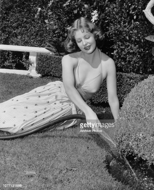American actress Arlene Dahl waters a small hedge in her garden circa 1950
