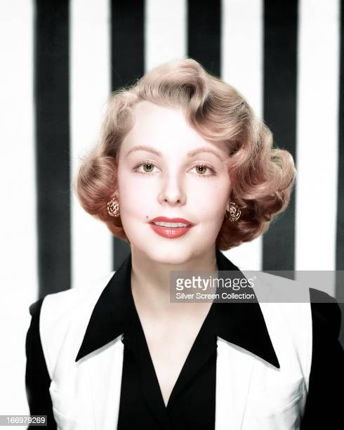 American actress Arlene Dahl wearing a black and white top and posing in front of a black and white striped background circa 1955