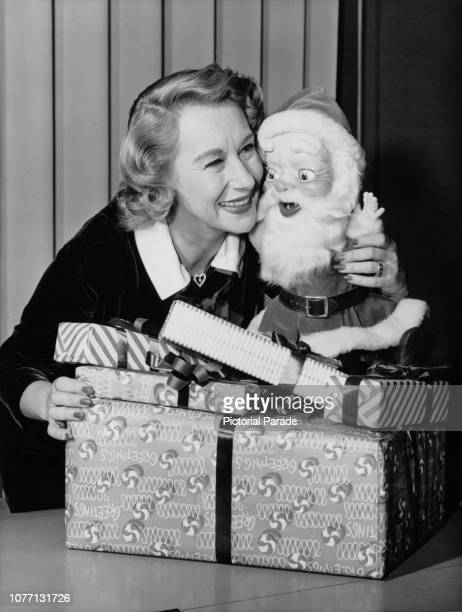 American actress Arlene Francis with a toy Santa Claus and a stack of presents at Christmas circa 1955