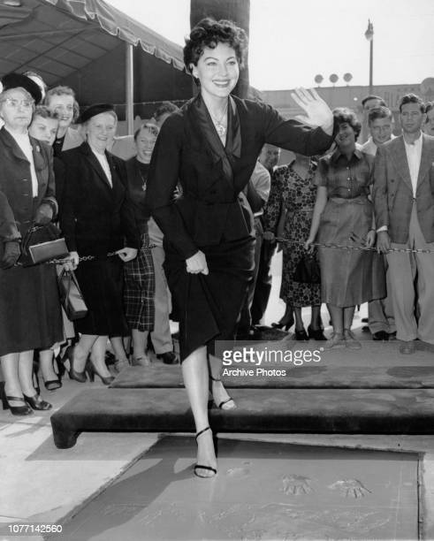 American actress Ava Gardner plants her footprints in wet cement outside Grauman's Chinese Theatre in Hollywood, 21st October 1952.