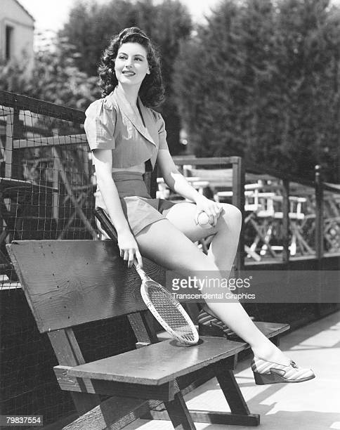 American actress Ava Gardner smiles as she sits perched on the backrest of a bench a tennis racquet in one hand and ball in the other 1948 She wears...