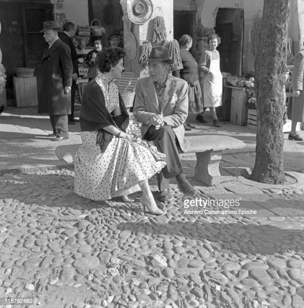 American actress Ava Gardner wearing a polkadotted dress gloves and a shawl sitting with the actor Humphrey Bogart on a bench in front of a shop in...
