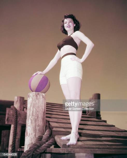 American actress Ava Gardner wearing white shorts a bra top and resting her hand on a beach ball circa 1950