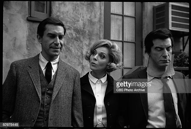 American actress Barbara Bain stands between her husband American actor Martin Landau and an actor who wears a mask with Landau's likeness in an...
