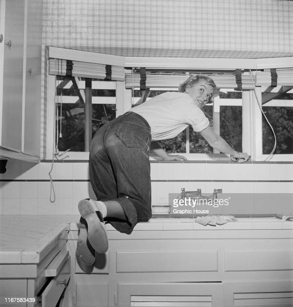 American actress Barbara Bel Geddes climbs on the sink to lower the kitchen blinds at her new home in Brentwood, California, circa 1950. She is...