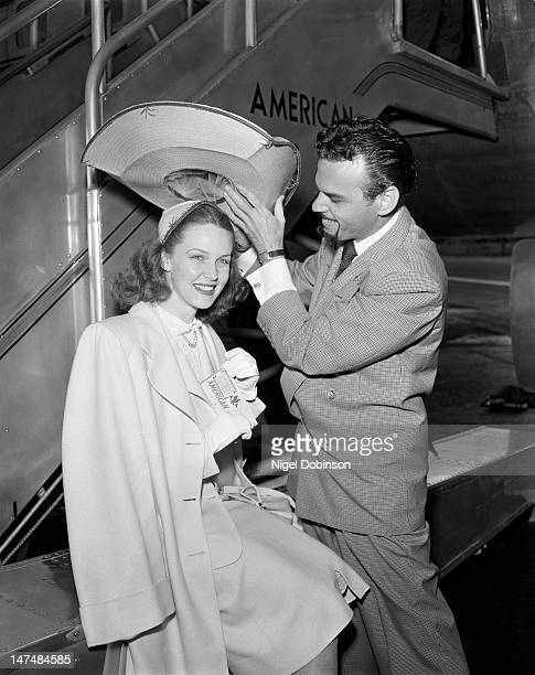 American actress Barbara Britton poses as an unidentified man with a goatee places an oversized hat on her head on the tarmac at Los Angeles...
