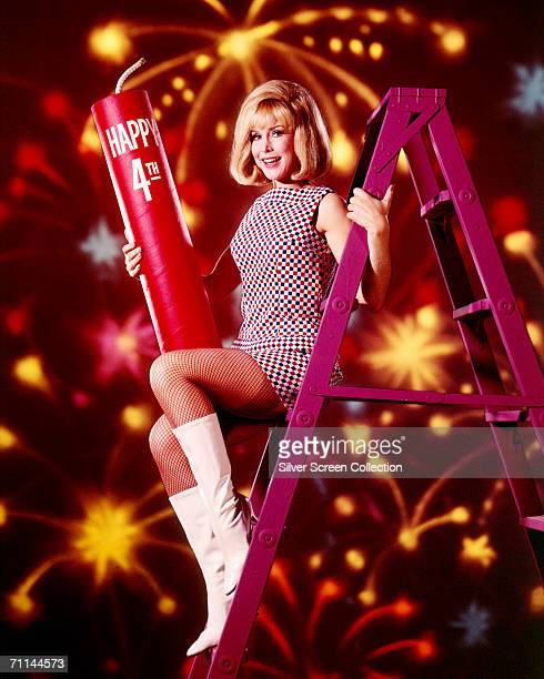American actress Barbara Eden celebrates the fourth of July up a purple stepladder with a giant firecracker circa 1965 Eden is best known for her...