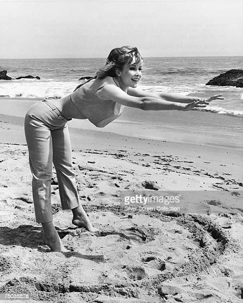 American actress Barbara Eden performs some stretching exercises on the beach circa 1965