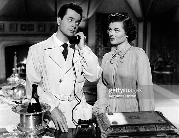 American actress Barbara Hale looking at American actor Larry Parks speaking over the phone in the film Emergency Wedding 1950