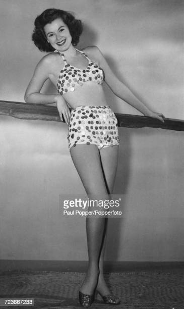 American actress Barbara Hale poses wearing a bathing suit adorned with dozens of coins donated by American servicemen stationed around the world Los...