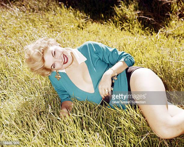 American actress Barbara Nichols reclining in shorts and a lowcut top circa 1955