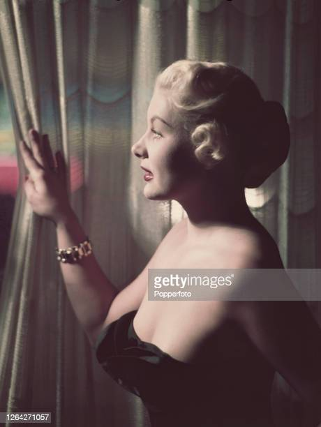 American actress Barbara Payton posed by a curtain in October 1952