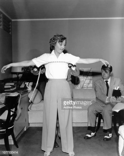 American actress Barbara Stanwyck has her measurements taken by a wardrobe fitter for her role in the Paramount Pictures film 'No Man of Her Own'...