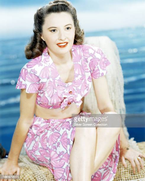 American actress Barbara Stanwyck in a pink and white twopiece beach outfit circa 1945