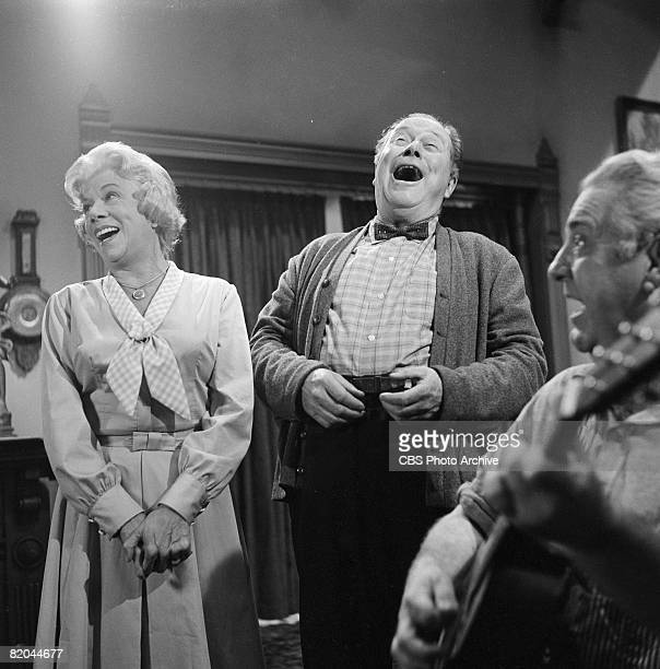 American actress Bea Benaderet as Kate Bradley and American actor Edgar Buchanan as Joseph P 'Uncle Joe' Carson sing with an unidentified guitarist...