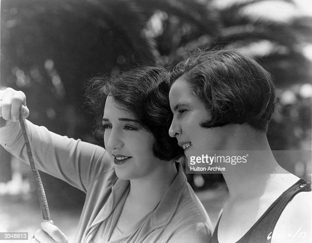 American actress Bebe Daniels shows American swimmer Gertrude Ederle the results of her first screen tests for the film 'Swim Girl Swim' circa 1927