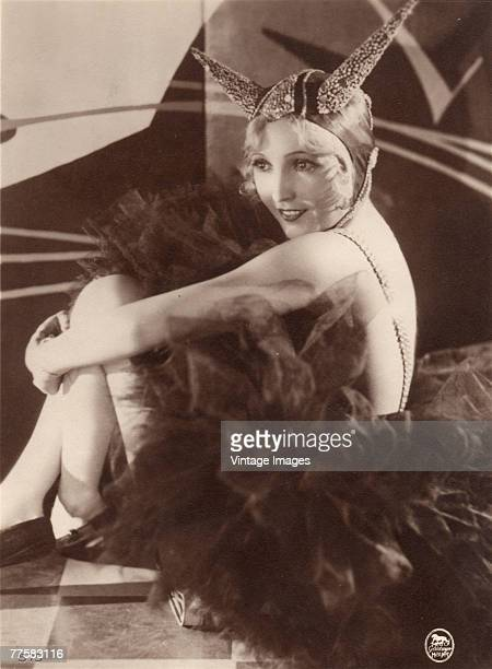 American actress Bessie Love hugs her knees to her chest as she sits on the floor in a frilly tutu skirt and a headpiece adorned with long horns mid...