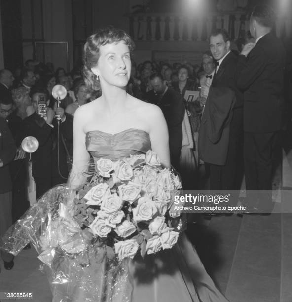 American actress Betsy Blair portrayed while wearing an evening dress and holding a flower bouquet Cannes 1955