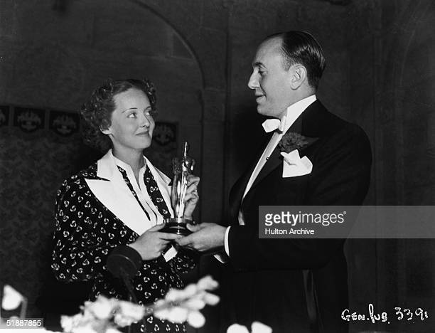 American actress Bette Davis and Canadianborn film producer Jack L Warner one of the founders of Warner Bros Pictures hold Davis's Oscar for Best...