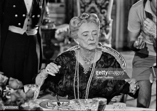 American actress Bette Davis dressed in a black lace dress with strings of pearls hanging down to her waist, an ornate pearl necklace around her neck...