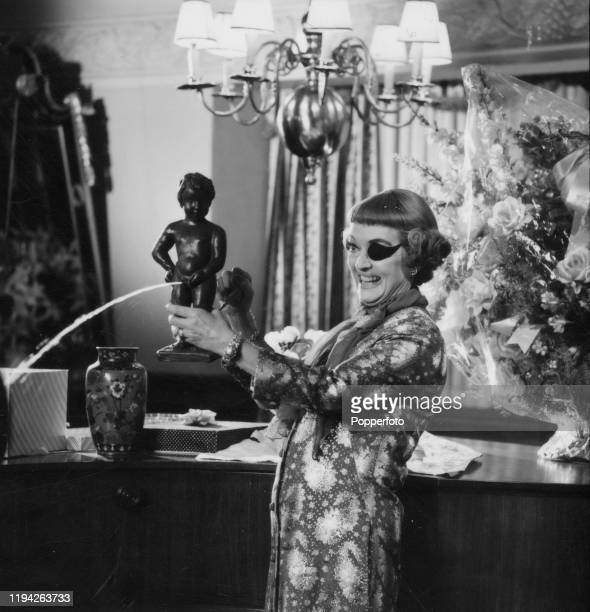 American actress Bette Davis grins as she activates a stream of water flowing from a replica Manneken Pis statue during an interview in England in...