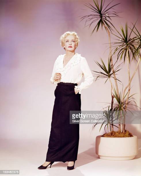 American actress Bette Davis in a black fulllength skirt and white blouse circa 1960