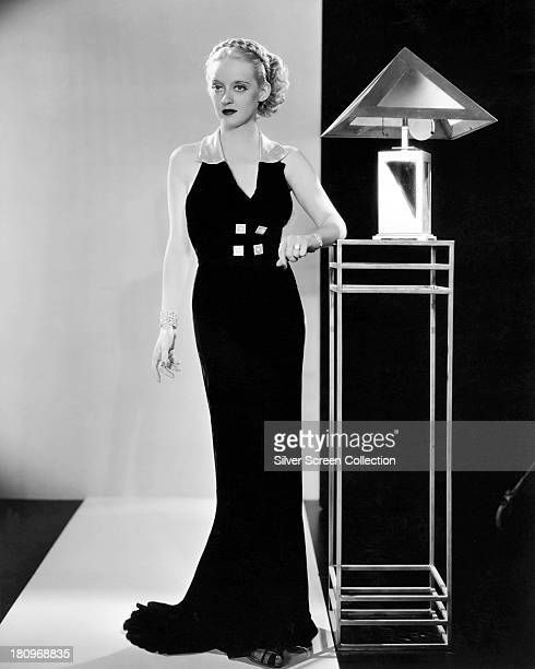 American actress Bette Davis posing in a black floorlength dress with contrasting collar and buttons next to an Art Deco lamp and table circa 1935