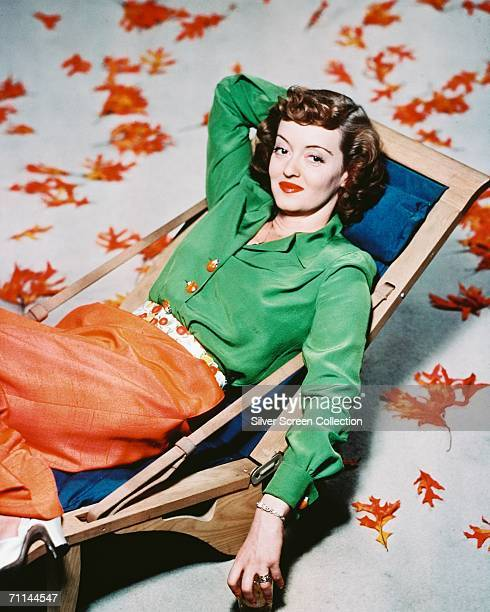 American actress Bette Davis relaxing in a deckchair surrounded by autumn leaves circa 1940