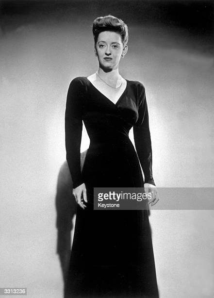 American actress Bette Davis wearing a black frost crepe dinner gown