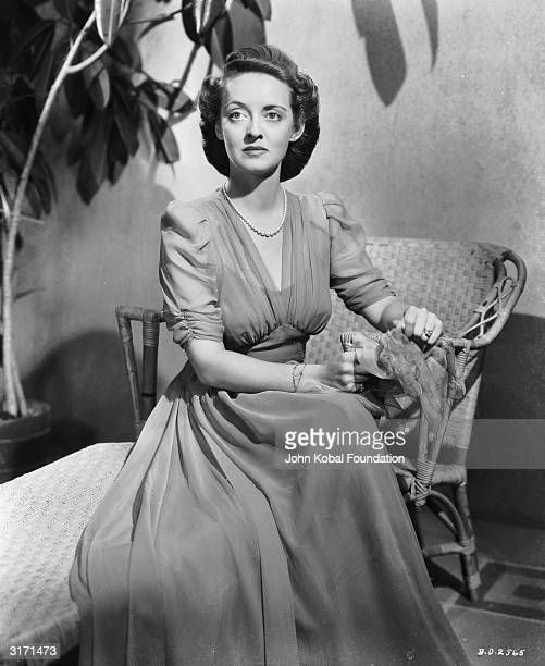 American actress Bette Davis wearing a long chiffon dress sits on a basket table in her role as Leslie Crosbie in William Wyler's film noir 'The...