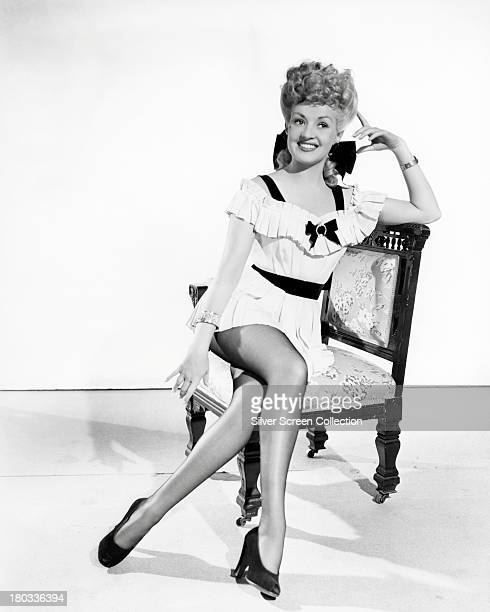 American actress Betty Grable wearing a short white pleated dress circa 1945