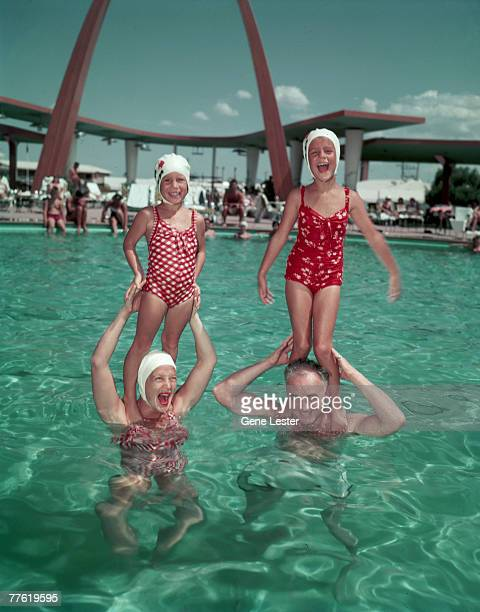American actress Betty Hutton and hotelier Wilbur Clark stand in the pool of Clark's hotel the Desert Inn and hold Hutton's daughters Lindsey and...