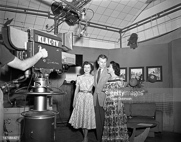 American actress Betty White actor Eddie Albert and an unidentified woman pose in front of the a KLACTV camera during a broadcast of the talk show...