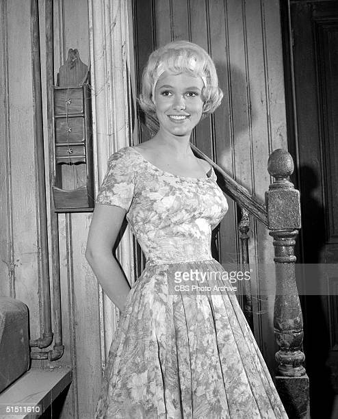 American actress Beverly Owen as 'Marilyn' leans against the wall in a floral print dress on the set of the CBS television situation comedy 'The...