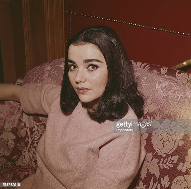 American actress Brigid Bazlen who plays the character of Dora Hawkins in the film 'How the West Was Won' posed sitting on a sofa in 1962