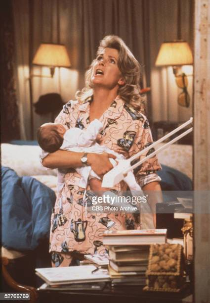 American actress Candice Bergen looks up to the heavens in desperation while holding an infant in an episode of the television series 'Murphy Brown'...