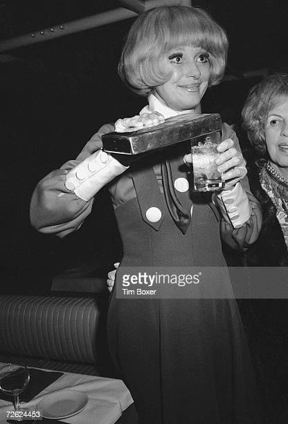 American actress Carol Channing pours herself a drink from a rectangular metal flask, late 1970s.