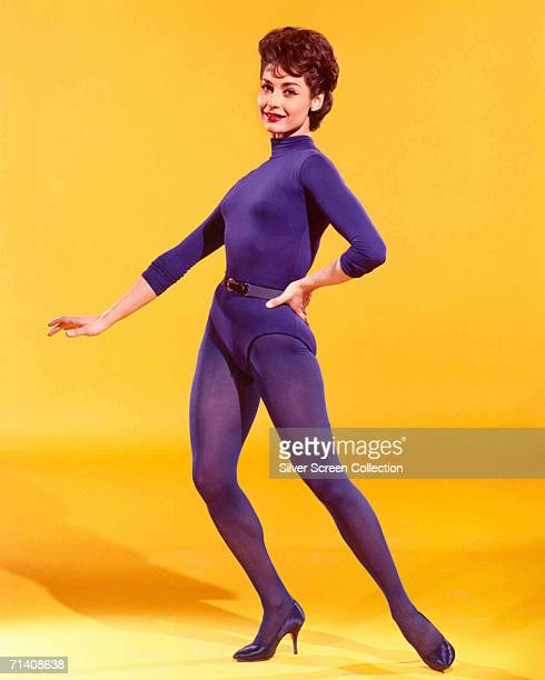 American actress Carol Lawrence wearing a purple leotard and matching tights against a yellow backdrop circa 1960