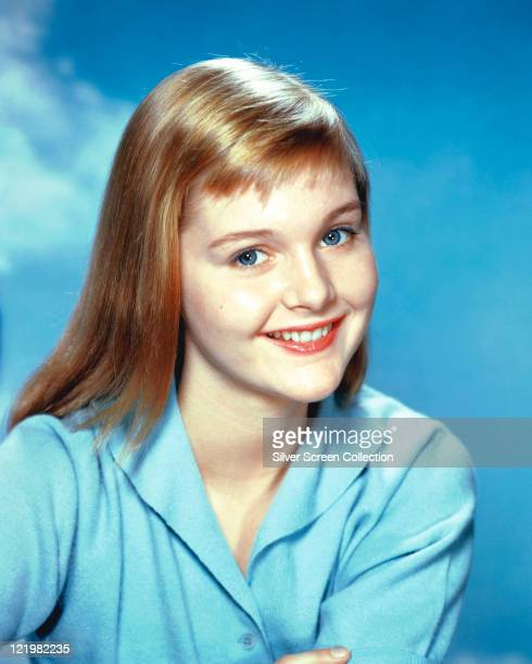 Sue Lyon US actress wearing a light blue blouse smiling in a studio portrait against a blue background circa 1960