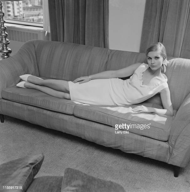 American actress Carol Lynley lies on a sofa, wearing a midi dress and heels, UK, 16th April 1965.